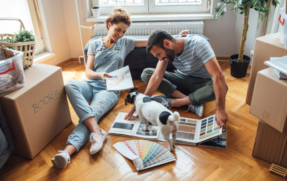 Husband and wife playing with a dog on their new home